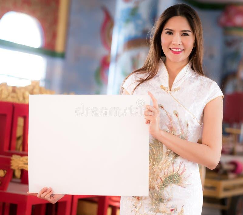 La mujer china asiática en chino tradicional lleva a cabo el espacio en blanco vacío fotos de archivo libres de regalías