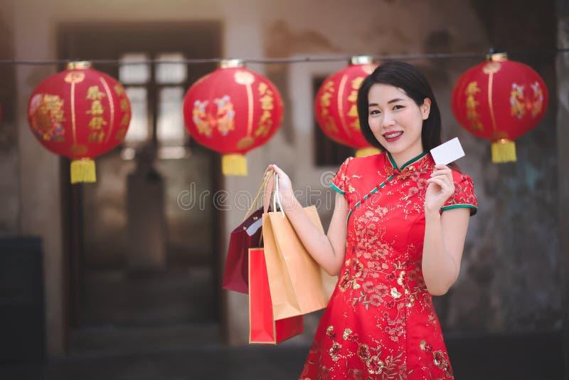 La mujer china asiática en el vestido rojo tradicional de Cheongsam que sostenía el bolso de compras y pagó vía crédito en Año Nu imagen de archivo