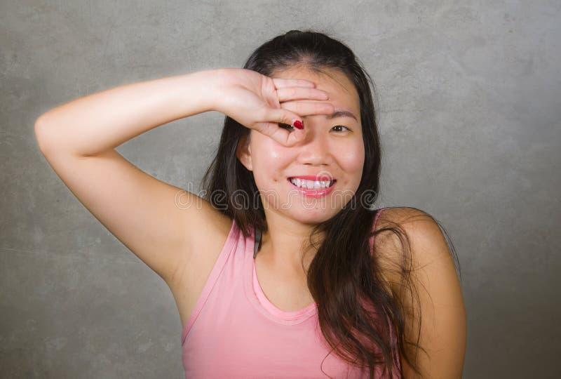 La mujer china asiática feliz y hermosa del adolescente que emula a los fingeres anuda el gesto de la celebración de la meta del  imagenes de archivo