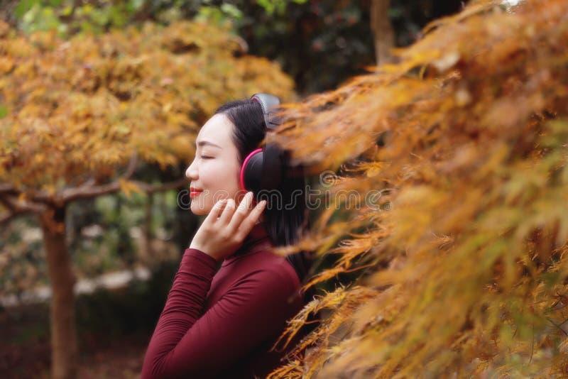 La mujer china asiática joven que escucha la música con los auriculares se sienta debajo de árbol imagen de archivo libre de regalías