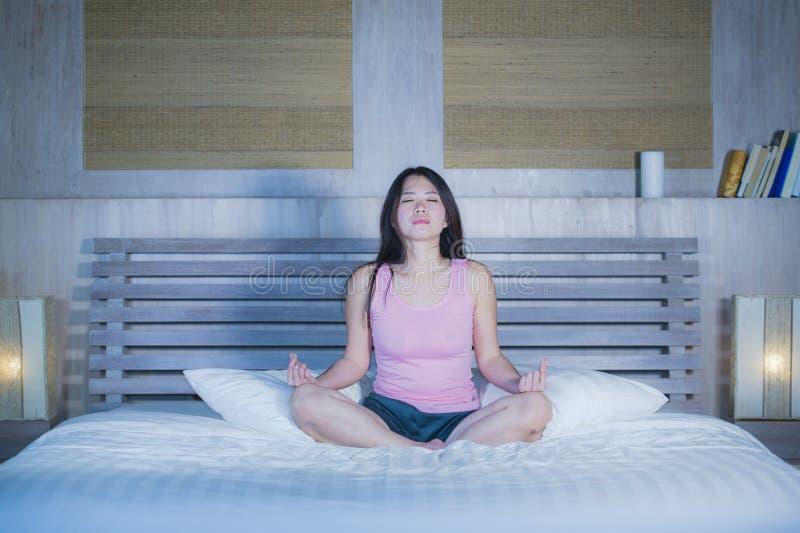 La mujer china bastante asiática 20s o 30s de los jóvenes que relaja en casa el dormitorio que se sienta en cama en la posición d fotos de archivo