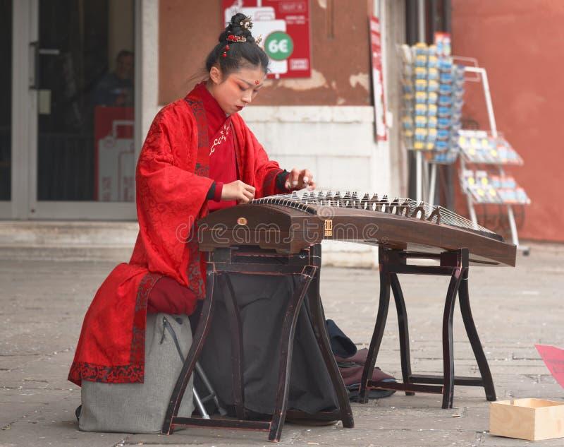 La mujer china está tocando un instrumento tradicional en Cannaregio fotografía de archivo