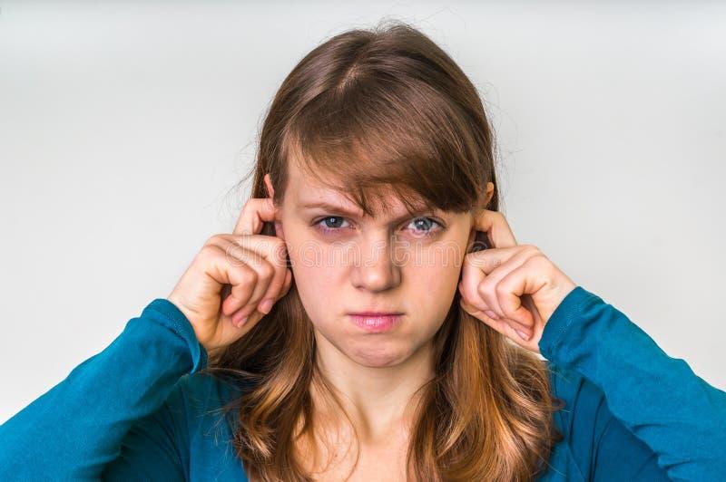 La mujer cierra los oídos con los fingeres para proteger contra fuerte ruido fotos de archivo