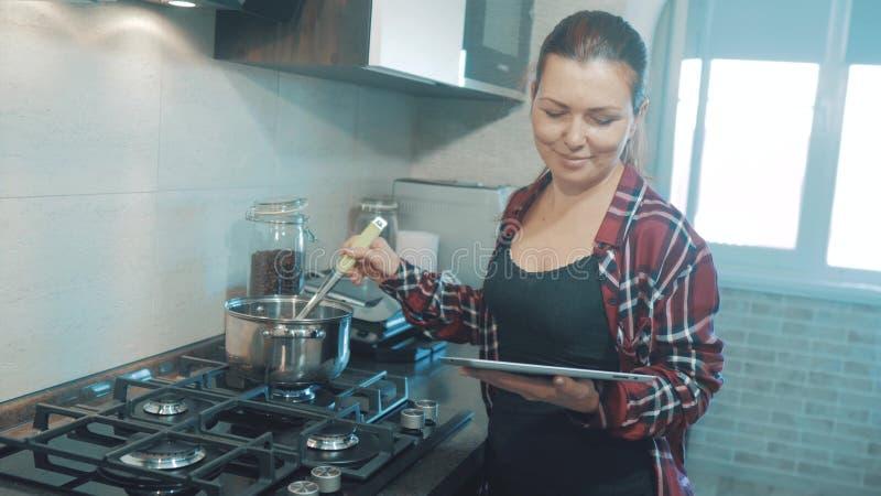 La mujer cocina la sopa en la cocina previene el agua en el pote y miradas en la receta en la tableta digital Mujer adentro imagen de archivo libre de regalías