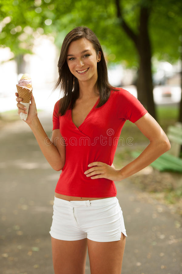 La mujer come el helado dulce al aire libre en parque imagen de archivo libre de regalías