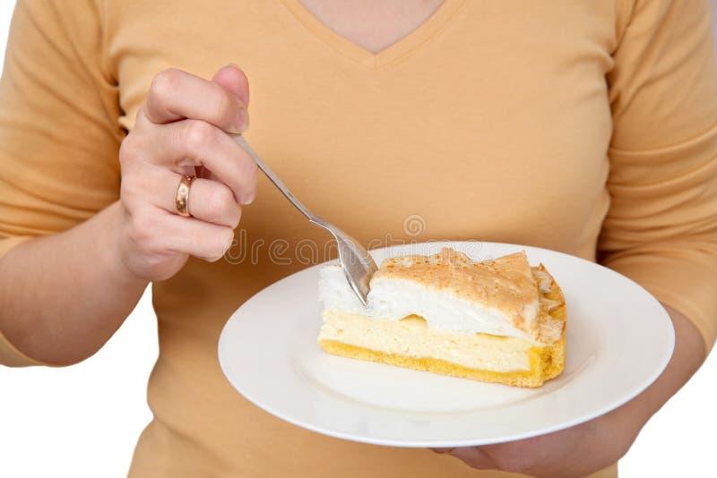 La mujer come el pastel de queso fotografía de archivo libre de regalías