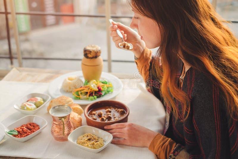 La mujer come la comida turca del kebab de la albóndiga y de la cerámica foto de archivo libre de regalías
