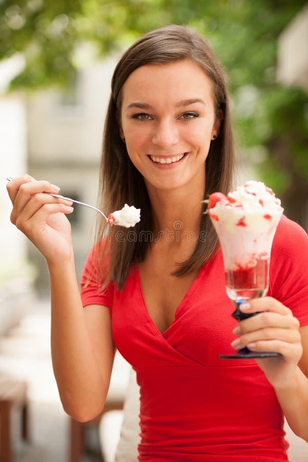 La mujer come la ensalada de fruta dulce de la fresa en un banco al aire libre en vagos fotos de archivo libres de regalías