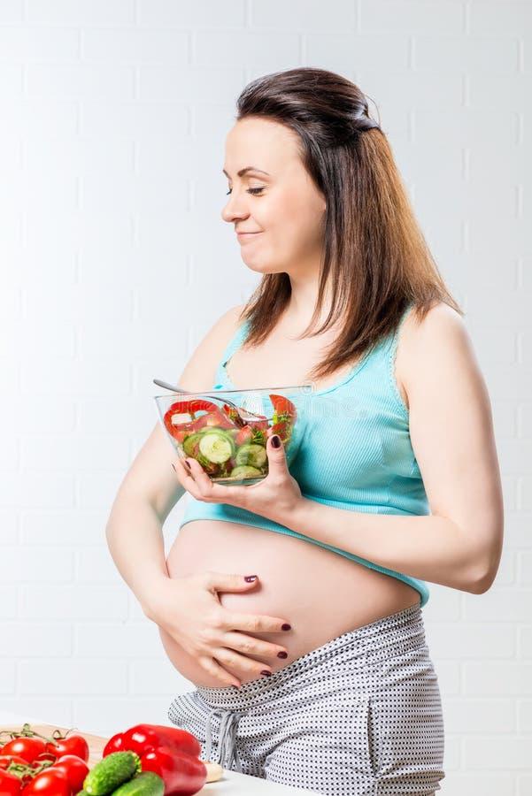 La mujer come una ensalada vegetal deliciosa fotos de archivo