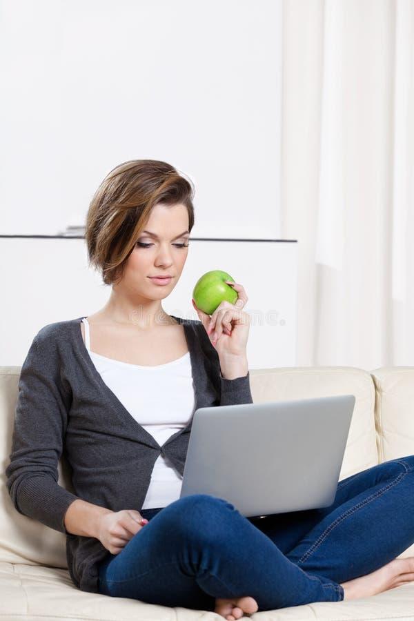 La mujer come una manzana verde que practica surf en el Internet fotografía de archivo libre de regalías