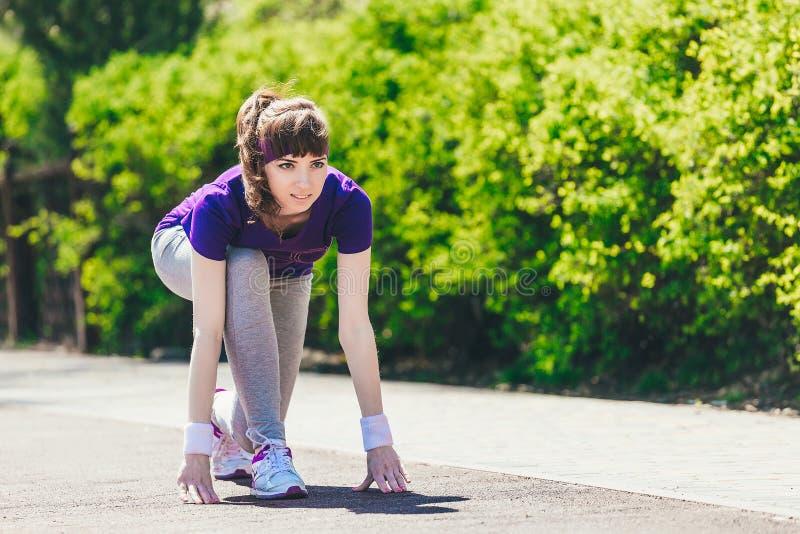 La mujer comienza a correr Una chica joven en ropa de deportes se prepara para correr en la naturaleza después de tomar un comien fotos de archivo