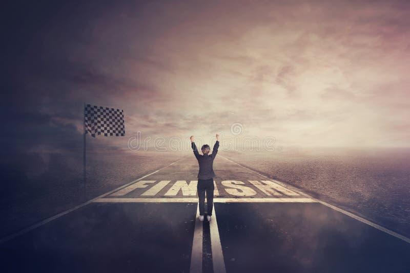 La mujer competitiva, aumentando las manos para arriba, celebra en el camino como cruzar la meta Concepto que gana del desafío su fotos de archivo