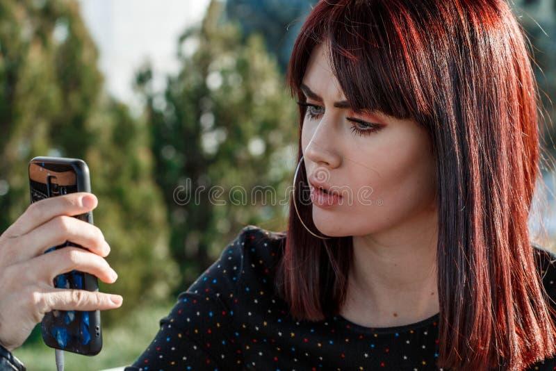 La mujer compone los cosméticos/a la chica joven hermosa compone el polvo de cara personalmente al aire libre fotografía de archivo libre de regalías