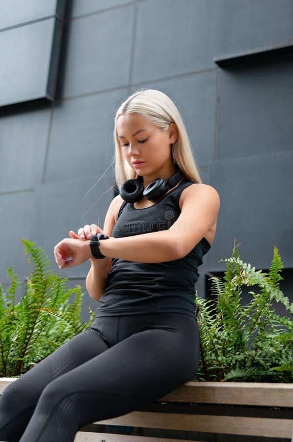 La mujer comprueba funcionamiento del entrenamiento en Smart Watch en ciudad imágenes de archivo libres de regalías