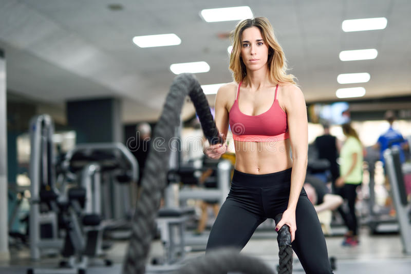 La mujer con batalla ropes ejercicio en el gimnasio de la aptitud fotos de archivo