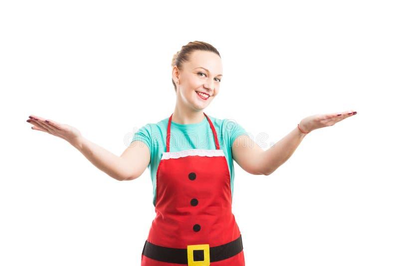 La mujer con el delantal rojo que hace la invitación y la presentación gesticulan fotos de archivo