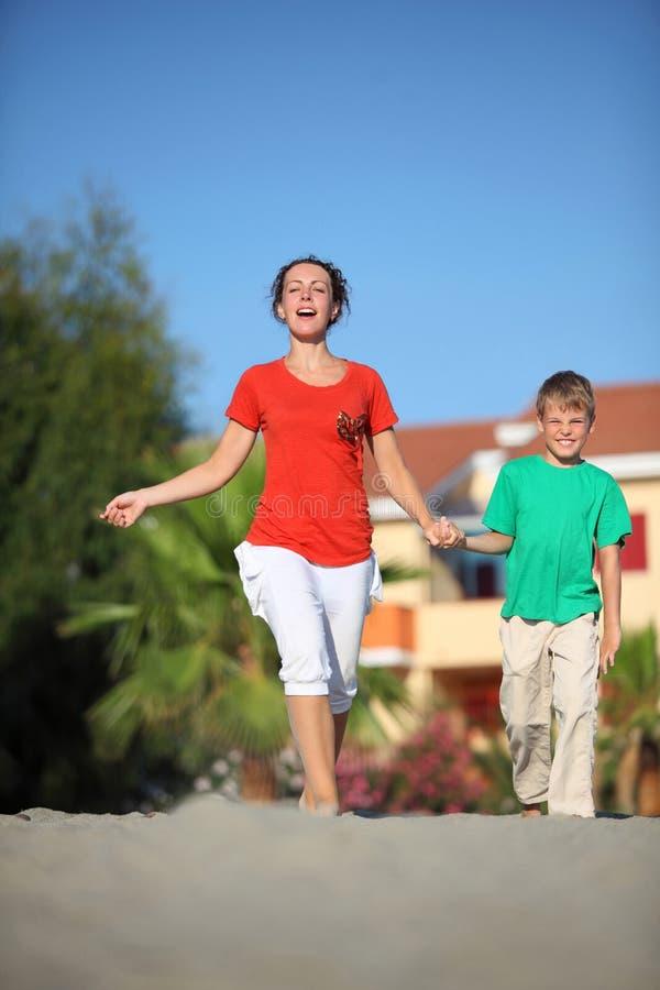 La mujer con el hijo que se aferra a las manos se apresura en la playa fotografía de archivo libre de regalías