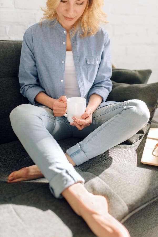 La mujer con el libro bebe el caf? en el sof? negro acogedor imagen de archivo