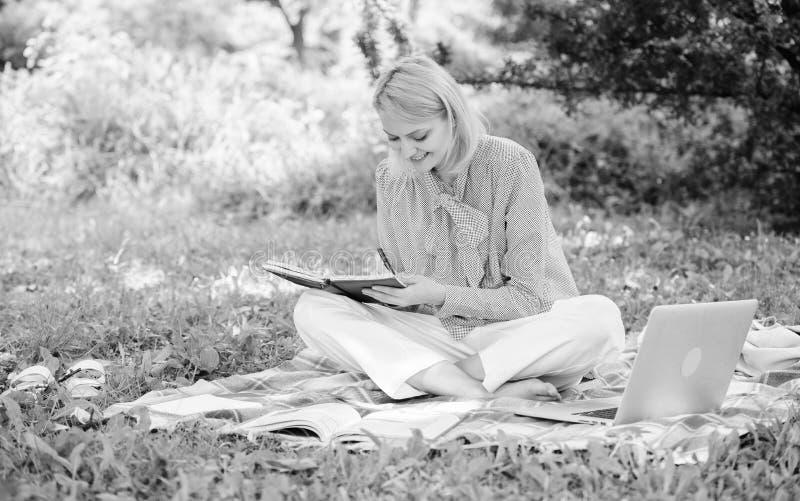 La mujer con el ordenador port?til se sienta en prado de la hierba de la manta La muchacha con la libreta escribe la nota Concept fotos de archivo