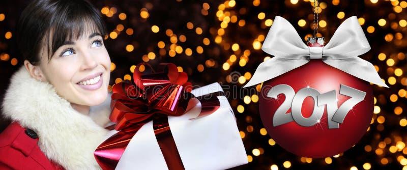 La mujer con el paquete del regalo de la Navidad, sonriendo y mira para arriba fotos de archivo