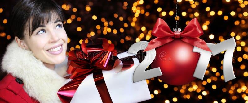 La mujer con el paquete del regalo de la Navidad, sonriendo y mira para arriba stock de ilustración
