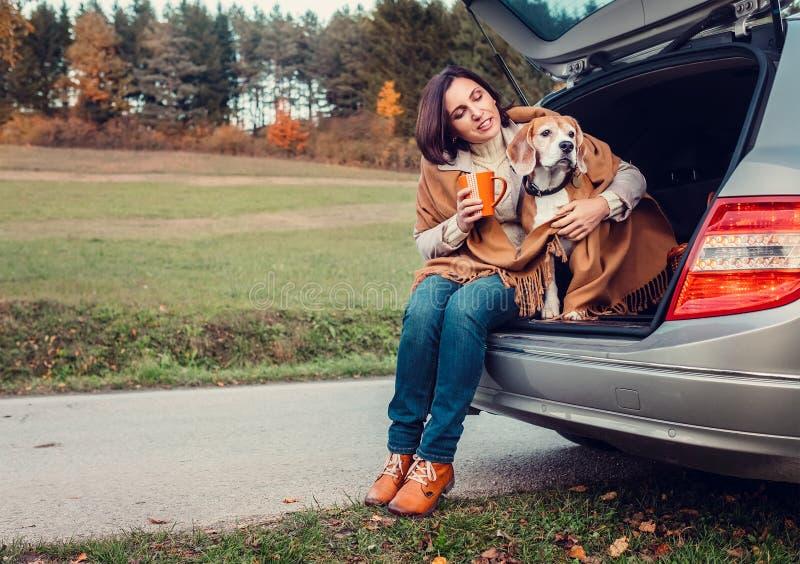La mujer con el perro se sienta junta en el camión del gato y calienta té caliente foto de archivo libre de regalías
