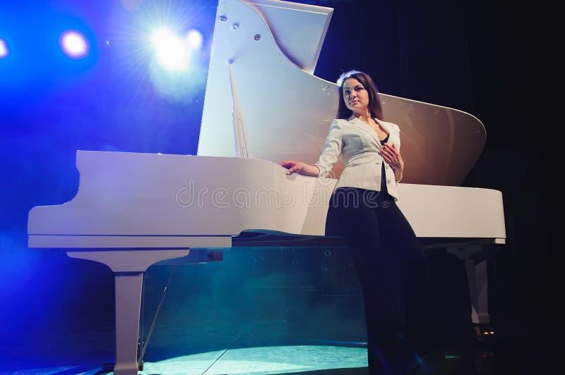 La mujer con el piano blanco Pianista hermoso en la etapa cerca del piano fotos de archivo libres de regalías