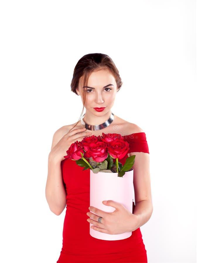 La mujer con el ramo de rosas rojas florece en la sonrisa rústica de la caja del vintage bonito imagen de archivo libre de regalías