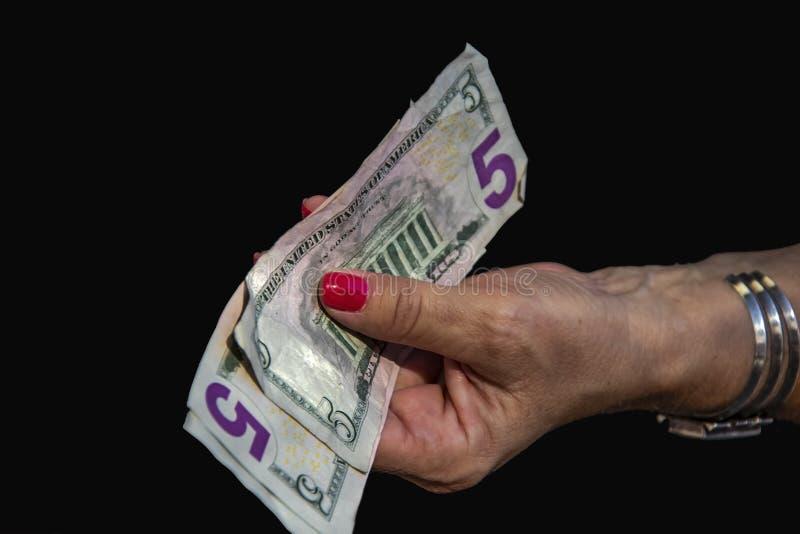 La mujer con el reloj del puño y las uñas rojas lleva a cabo varios cinco billetes de dólar USD con la escritura amarilla ilegibl imagen de archivo
