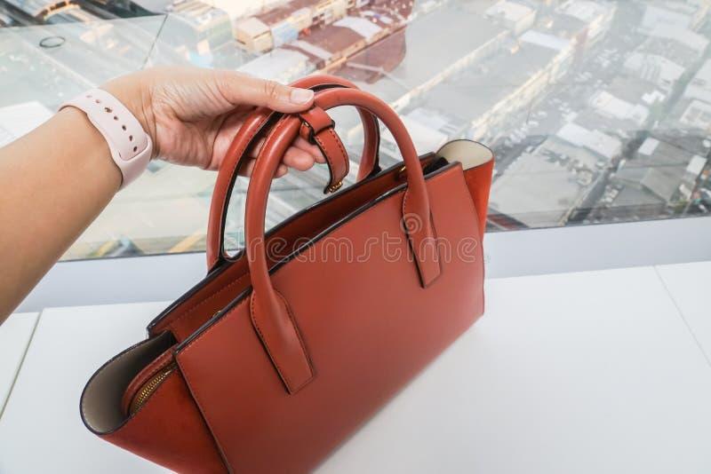 La mujer con el reloj rosado sostiene el bolso de cuero anaranjado de moda con la mano izquierda para el trabajo imagen de archivo libre de regalías