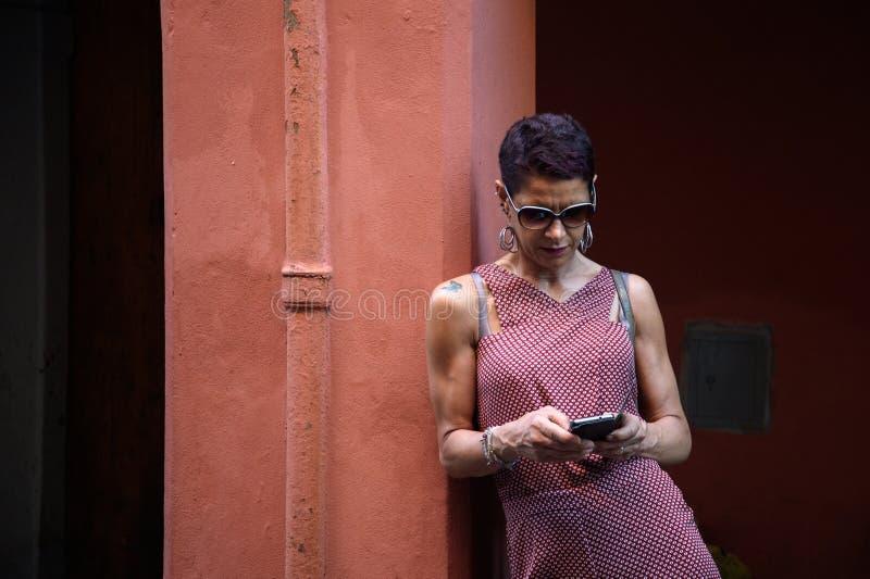 La mujer con el teléfono envía SMS fotos de archivo libres de regalías