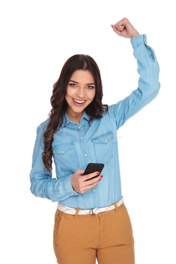 La mujer con el teléfono móvil celebra éxito imágenes de archivo libres de regalías