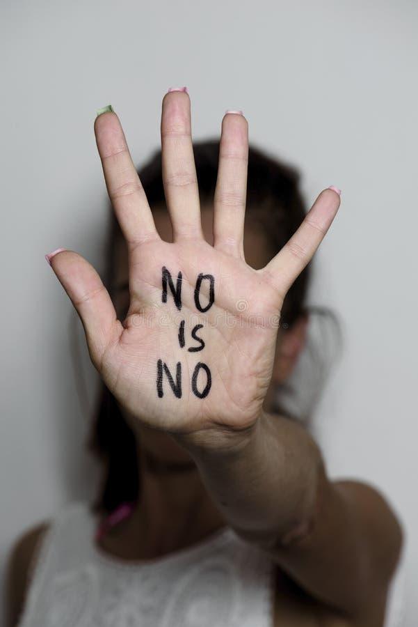 La mujer con el texto ningún es ningún escrito en su palma imagen de archivo
