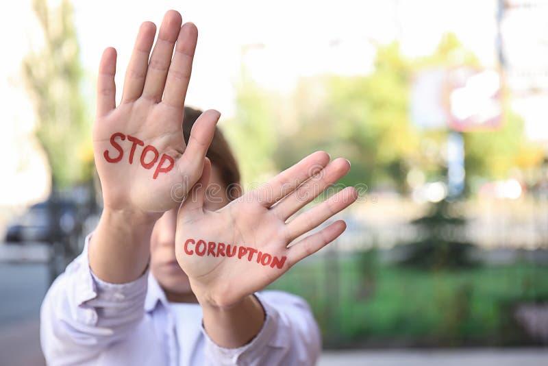 La mujer con el texto PARA LA CORRUPCIÓN escrita en sus palmas al aire libre fotos de archivo