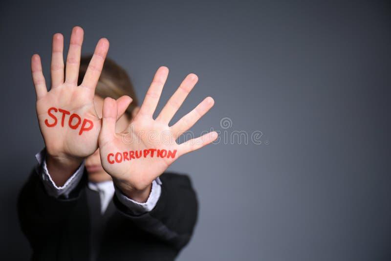 La mujer con el texto PARA LA CORRUPCIÓN escrita en sus palmas contra fondo gris foto de archivo libre de regalías
