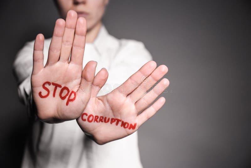 La mujer con el texto PARA LA CORRUPCIÓN escrita en sus palmas contra el fondo gris, primer foto de archivo