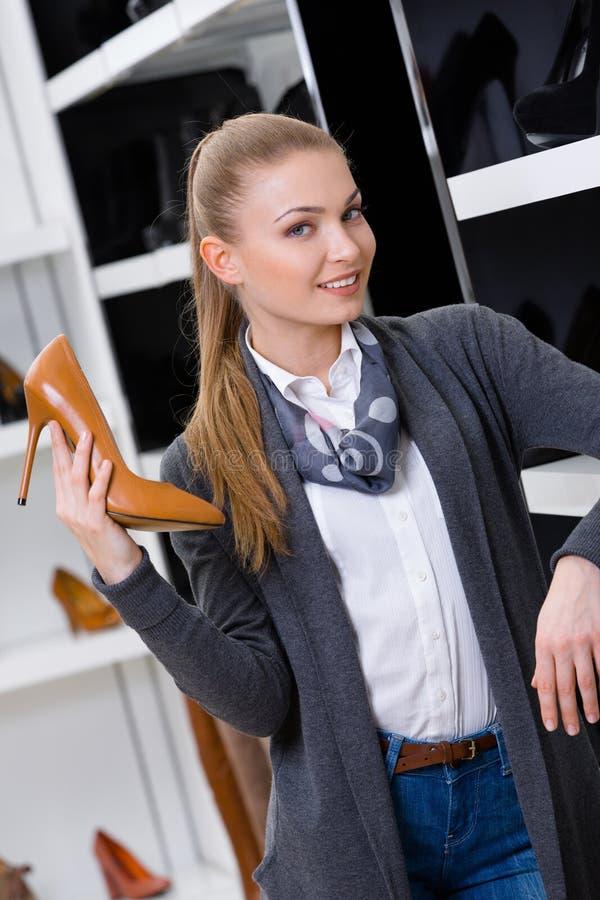 La mujer con el zapato a disposición elige calzado fotos de archivo libres de regalías