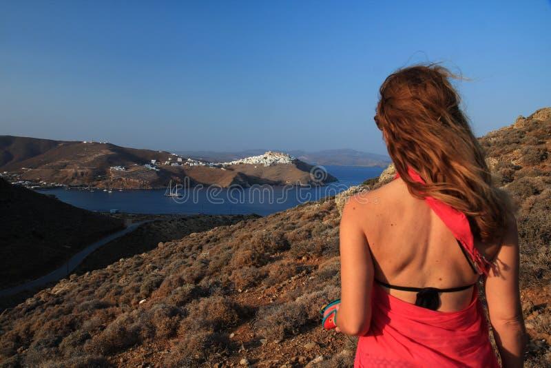 La mujer con ella detrás dio vuelta a la cámara en una isla griega fotografía de archivo