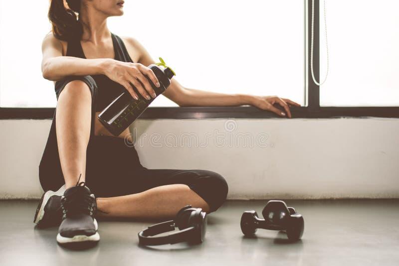 La mujer con entrenamiento de la forma de vida del ejercicio de la pesa de gimnasia y del dispositivo en la fractura de la aptitu fotos de archivo