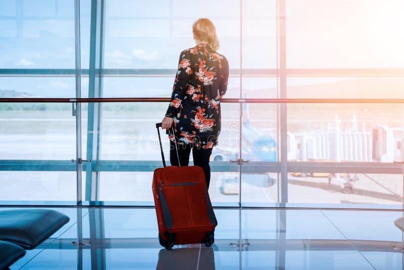 La mujer con equipaje en aeropuerto est? esperando el avi?n fotografía de archivo libre de regalías