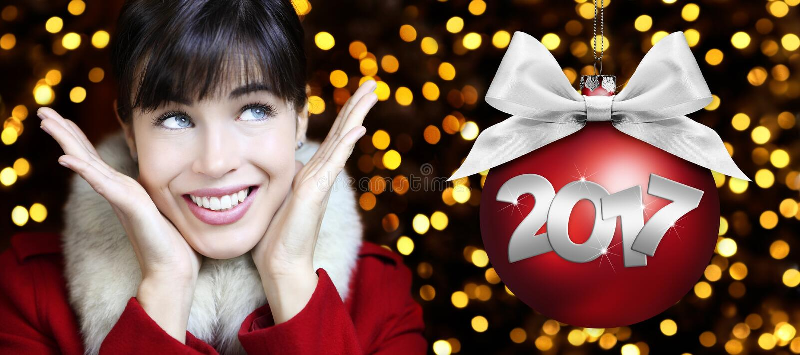 La mujer con la bola roja de la Navidad, sonriendo y mira para arriba en luces libre illustration