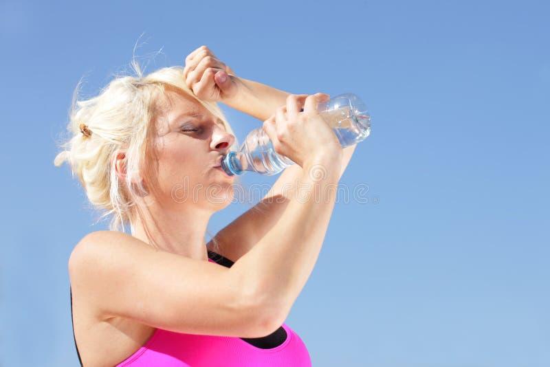 La mujer con la botella de agua siente el calor del verano fotos de archivo