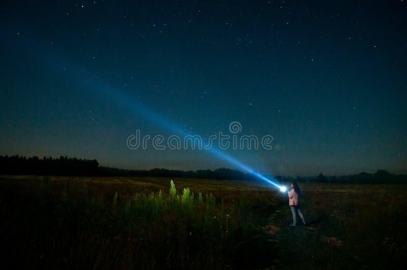 La mujer con la linterna entre las estrellas imagen de archivo libre de regalías