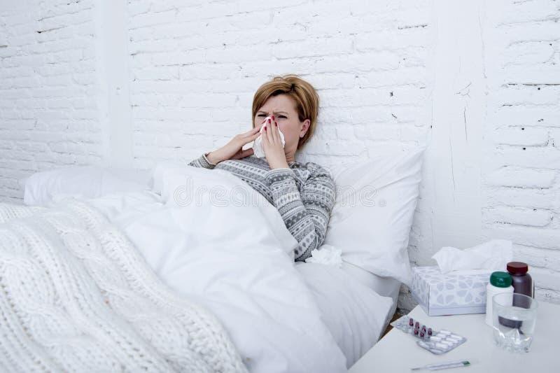 la mujer con la nariz de estornudo que sopla en tejido en la cama que sufre los síntomas fríos del virus de la gripe que tienen m foto de archivo libre de regalías