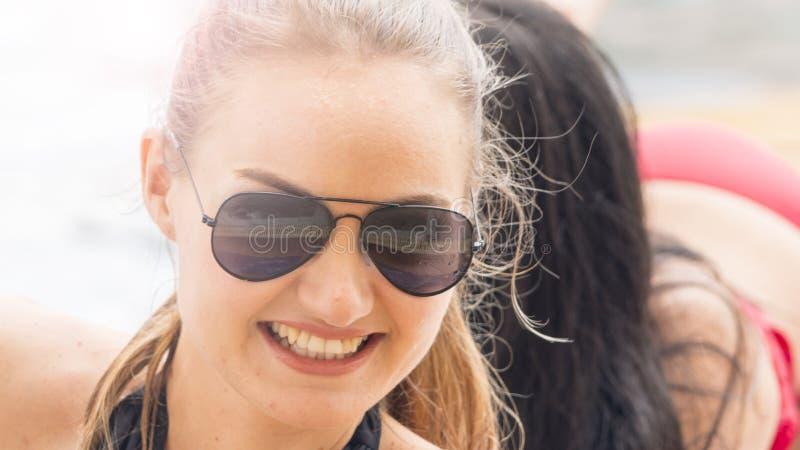 La mujer con las gafas de sol en desgaste de la natación consigue la piscina del partido con feeli foto de archivo