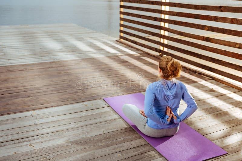 La mujer con las palmas dobladas que hacen yoga de la mañana imagen de archivo
