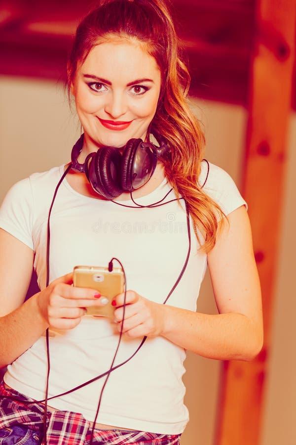 La mujer con los auriculares elige música en smartphone imágenes de archivo libres de regalías