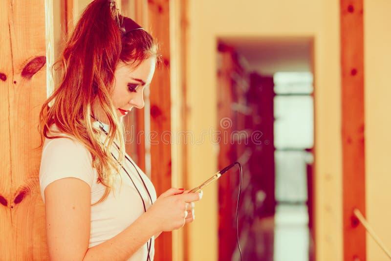 La mujer con los auriculares elige música en smartphone fotos de archivo