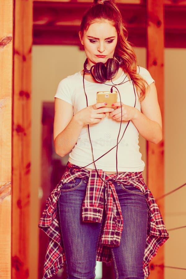 La mujer con los auriculares elige música en smartphone imagen de archivo