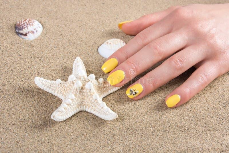 La mujer con los clavos amarillos manicure estrellas de mar conmovedoras del pulimento en arena de mar en la playa imagenes de archivo